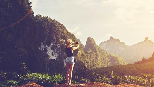Devojka stoji na vrhu brda i mobilnim telefonom fotografiše planinski predeo