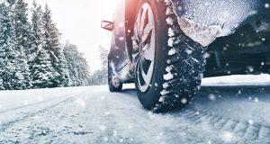 Vozač vozi automobil kroz teško prohodne puteve na planini dok pada sneg. Iza sebe ostavlja trag zimskih guma