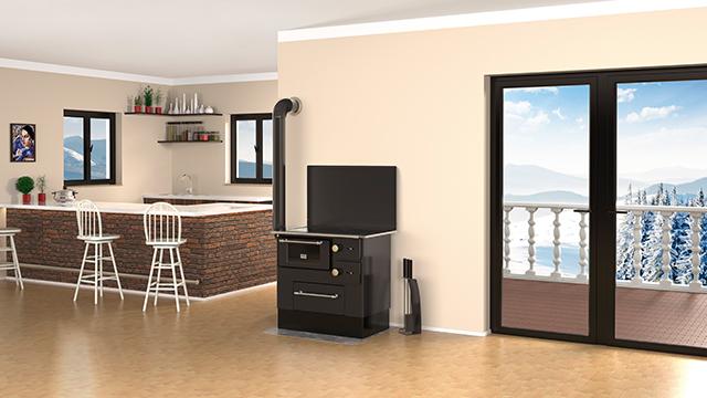 Crni šporet na drva, u prostranoj dnevnoj sobi sa kuhinjom, pored terasnih vrata sa pogledom na zimski pejzaž