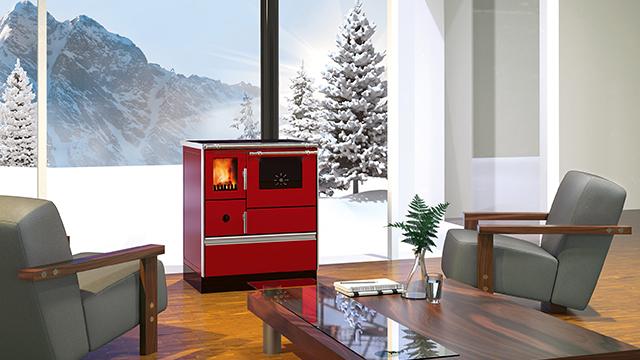 Crveni šporet na drva sa staklom na vratima kroz koje se vidi kako gori vatra, u prostranoj dnevnoj sobi sa pogledom na planinu i četinare prekrivene snegom