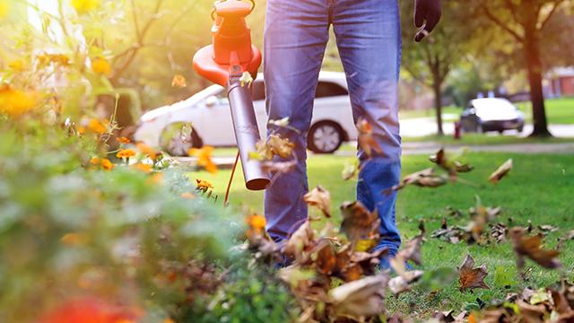 Muškarac sa duvačem za lišće sređuje dvorište ispred kuće
