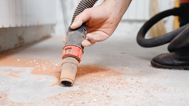 Majstor uz pomoć usisivača za pepeo usisava prljavštinu na podu nastalu usled bušenja zida