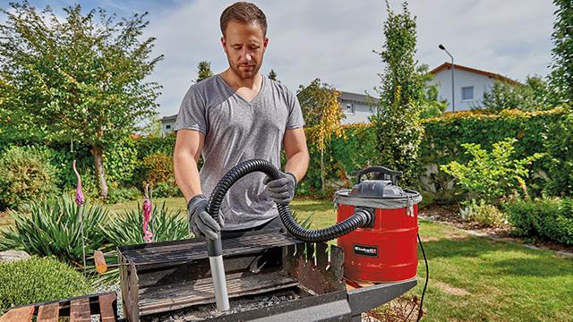 Mlad momak stoji u dvorištu na travi i usisava pepeo iz roštilja usisivačem za pepeo