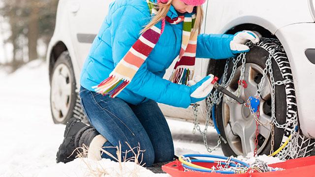 Mlada devojka u plavoj zimskoj jakni i šarenom šalu, naslonjena je na kolena I montira lance za sneg na zimske gume svog automobila. Pored nje nalazi se i crvena kutija u kojoj se lanci za sneg nalaze