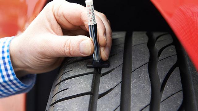 Muškarac koristi merač dubine šare gume, kako bi proverio da li odgovara zakonskim propisima i da li poseduje propisan TWI