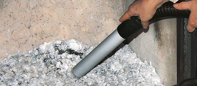 Muškarac usisava pepeo iz kamina usisivačem pepela