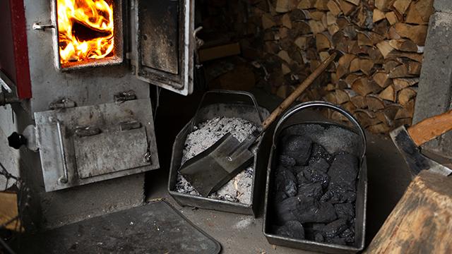 U nadstrešnici iza kuće smeštena je peć pored složenih drva. Vrata peći su otvorena i vidi se kako drva gore. Pored peći nalaze se kanta sa pepeom i lopatom, kanta sa ugljem i sekira zabodena u panj