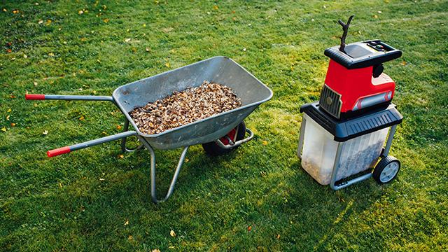 Seckalica za grane na travnjaku i kolica sa piljevinom pored nje