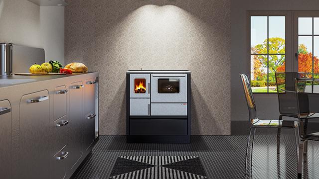 Belo-crni šporet sa staklom na vratima kroz koje se vidi vatra, postavljen u moderno opremljenu, metalik sivu kuhinju