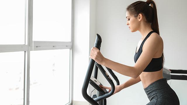 Mlada devojka u sportskoj opremi podešava intenzitet treninga na displeju eliptičnog trenažera koji je postavljen pored prozora