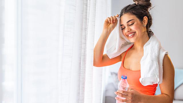 Nasmejana devojka stoji pored prozora sa zavesom, drži flašicu vode i briše čelo peškirom zadovoljna urađenim treningom