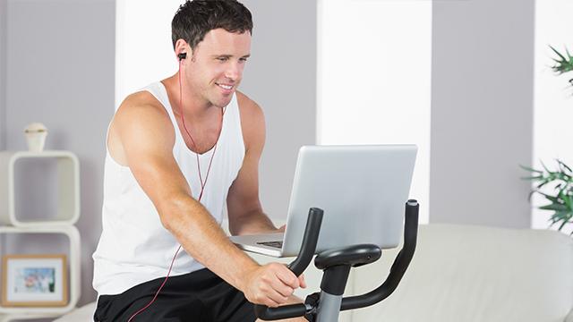 Nasmejani muškarac u šorcu i atlet majici sa slušalicama vežba na sobnom biciklu u dnevnoj sobi