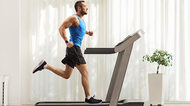 Muškarac u sportskoj opremi intenzivno trči na traci za trčanje postavljenoj u prostoriji sa sobnom biljkom i dugom belom zavesom celom dužinom zida