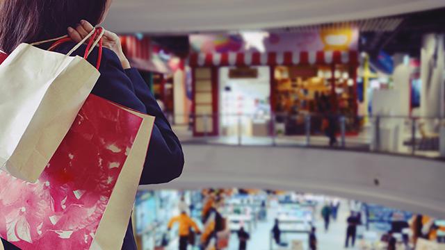 Devojka u šoping centru okrenuta leđima, sa rukom preko ramena u kojoj drži kese iz šopinga