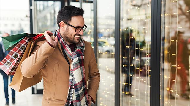 Muškarac u kaputu prolazi pored novogodišnjeg izloga i u ruci nosi kese sa poklonima