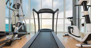 Traka za trčanje, eliptični trenažer i sobni bicikl u kući, u prostoriji sa drvenim podom