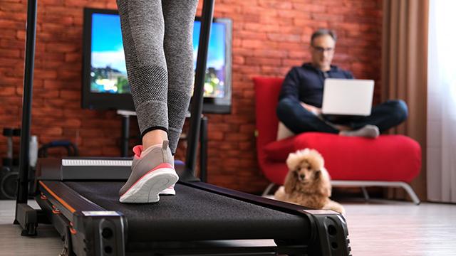 Žena vežba na traci za trčanje u dnevnoj sobi, u uglu na fotelji sedi muž i radi za računarom, na podu je kuče