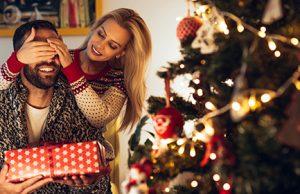 Mladi par u prazničnim džemperima stoji ispred novogodišnje jelke sa crvenim ukrasima i svećicama. Devojka je rukama momku zatvorila oči, dok momak u rukama drži poklon u ukrasnoj kutiji crvene boje sa belim zvezdicama i crvenom mašnom