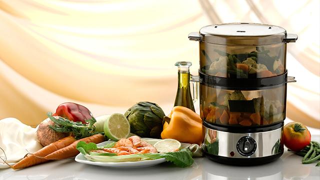 Aparat za kuvanje na pari na dva sprata, napunjen povrćem i okružen ukusnim zdravim namirnicama za pripremu