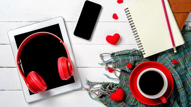 Na drvenom belom stolu tablet, crvene slušalice na njemu, crvena šoljica sa kafom, sve u znaku Dana zaljubljenih