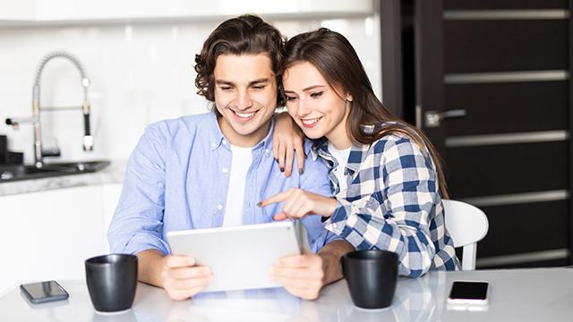 Devojka i dečko u kuhinji za stolom piju kafu i gledaju nešto na tabletu