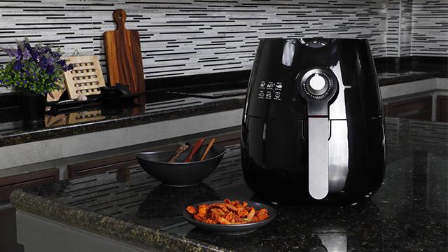 Friteza bez ulja ucrnoj boji na kuhinjskom pultu pored tanjira sa hrskavim grickalicama