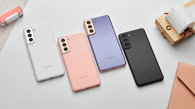 Na stolu su poređana četiri modela iz nove Samsung Galaxy S serije - fantomski beli i roze S21, kao i ljubičasti i crni S21+. Prikazane su njihove zadnje kamere smeštene u Contour Cut kućište