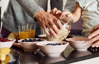Porodica priprema zdrav obrok sa voćem i žitaricama