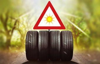 Četiri letnje gume poređane na putu, iznad njih je trouglasti saobračajni znak na kom je nacrtano sunce