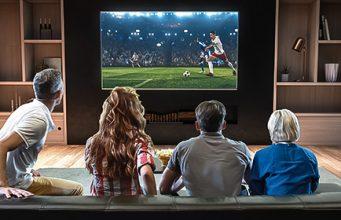 Grupa ljudi sedi ispred televizora i gleda fudbalsku utakmicu na velikom ekranu