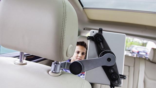 Dečak, udobno smešten na zadnjem sedištu automobila, gleda u tablet postavljen na auto-držač