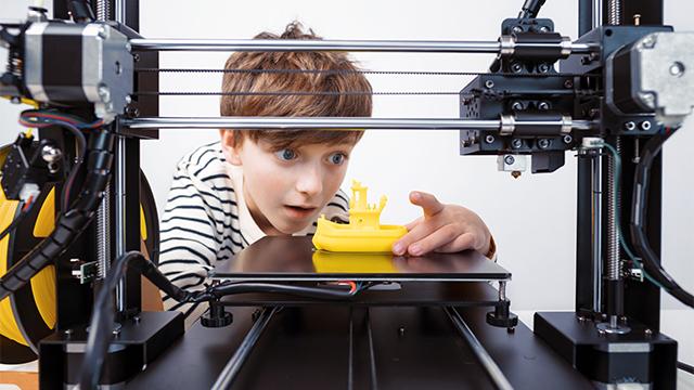 Dečak zadivljeno gleda i dodiruje figuru broda odštampanu u 3D štampaču