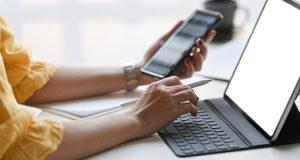 Ženska ruka u jednoj ruci drži pametni telefon, a drugom kuca na tastaturi tableta koja je deo futrole