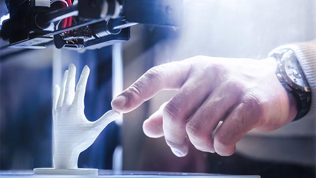 Čovek prstom dodiruje prst šake odštampane u 3D šampaču