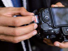 Čovek ubacuje memorijsku karticu u foto-aparat