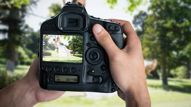 Foto-aparat u rukama slika devojku u venčanici dok se ljulja