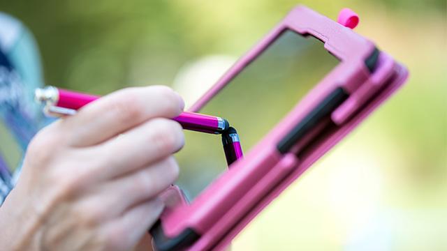Ženska osoba jednom rukom drži tablet u roze futroli, a u drugoj ruci drži olovku kojom piše po ekranu tableta