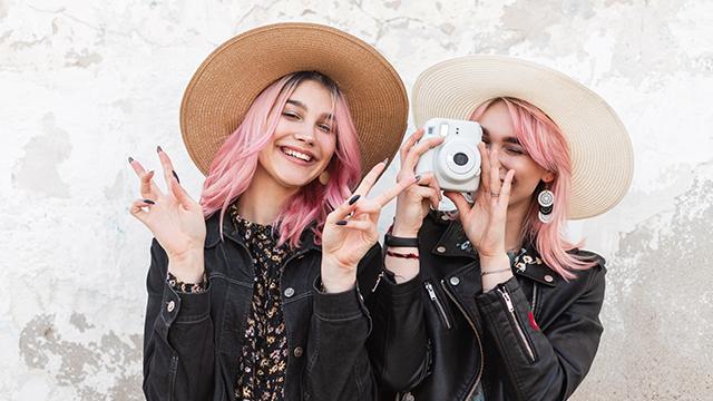 Dve devojke, drugarice, poziraju i slikaju se polaroid foto-aparatom