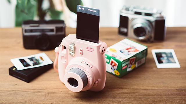 Na drvenom stolu Instax aparat, kutija sa foto-papirom, gotove fotografije