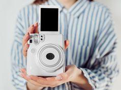 Devojka u košulji drži beli Instax foto-aparat sa foto-papirom koji se upravo ubacuje u aparat