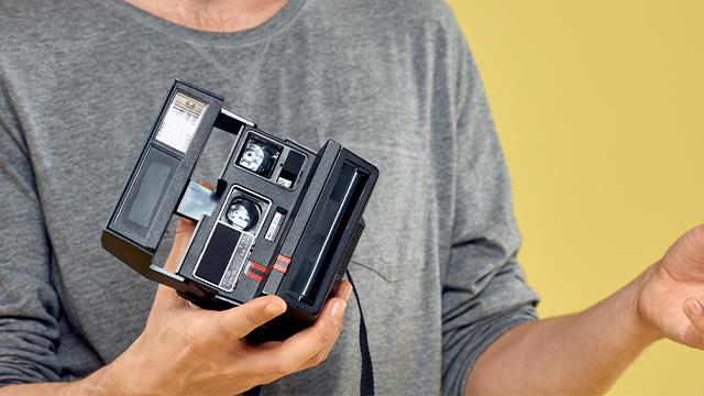 Muškarac koji u rukama drži polaroid foto-aparat crne boje