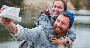 Dečko i devojka u prirodi prave selfi polaroid foto-aparatom