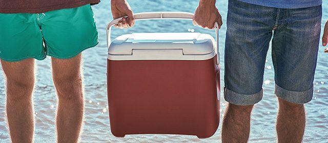 Prijatelji nose crveni ručni frižider na plaži