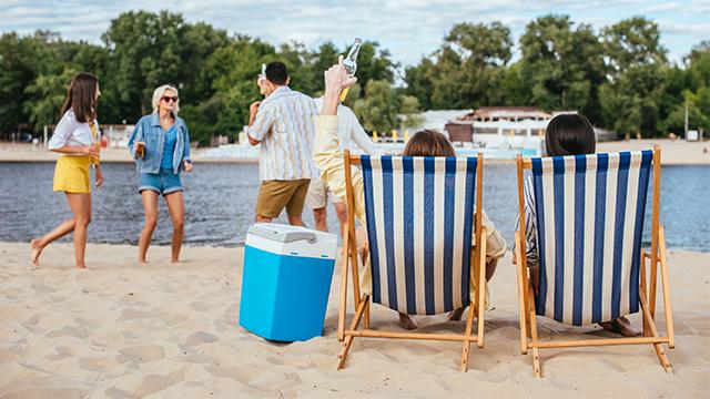 Društvo uživa u hladnom piću i zabavi na plaži uz ručni frižider