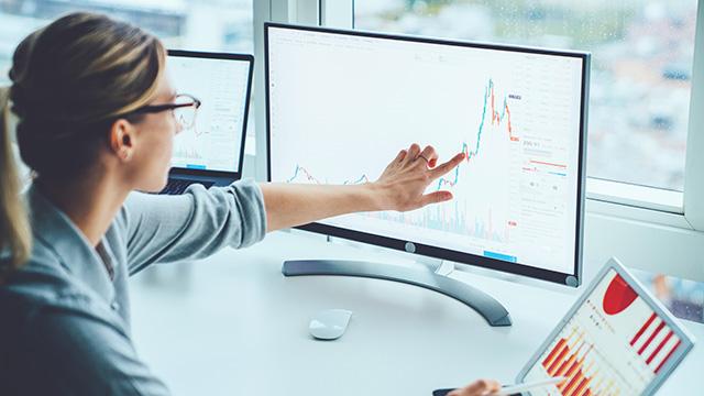 Devojka na monitoru sa touchscrinom prstom pomera kursor po ekranu