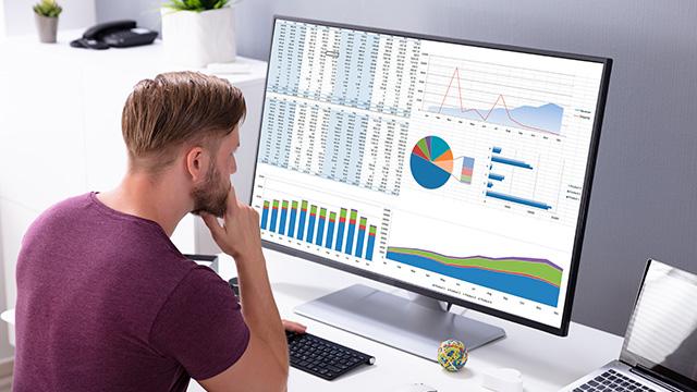 Dečko na poslu radi i gleda na monitoru tabele i grafikone