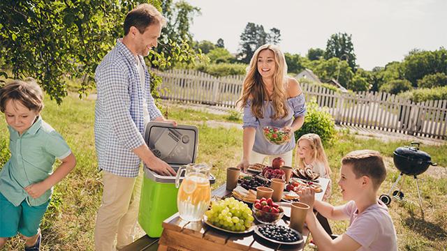 Nasmejana porodica uživa u prirodi i svežem voću. Muškarac vadi hranu iz ručnog frižidera
