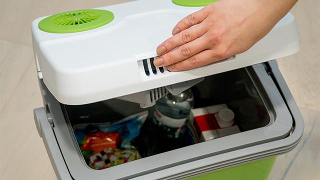Ženska ruka zatvara poklopac na spakovanom ručnom frižideru