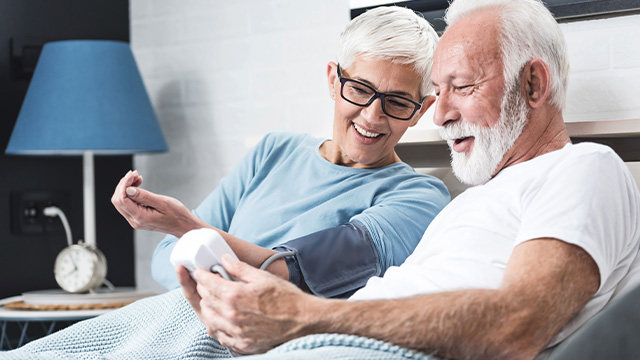 Muškarac sa sedom kosom i bradom udobno smešten u svom domu meri pritisak svojoj supruzi