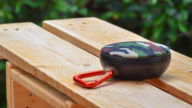 Atraktivni bežični zvučnik sa military dezenom i narandžastom alkom za kačenje nalazi se na klupi u parku